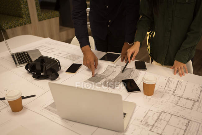 Business colleagues discussing over blueprint in office — Stock Photo