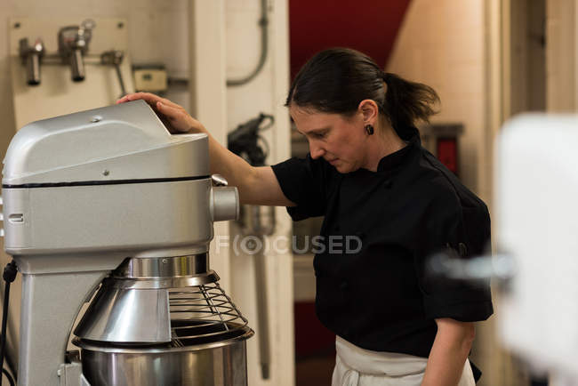 Chef using whisking machine in commercial kitchen — Stock Photo