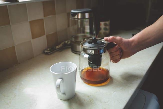 Frasco de filtro de café na mão masculina e caneca na bancada da cozinha em casa . — Fotografia de Stock