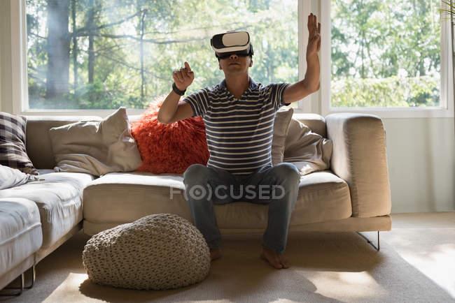 Homem usando fone de ouvido realidade virtual na sala de estar em casa — Fotografia de Stock