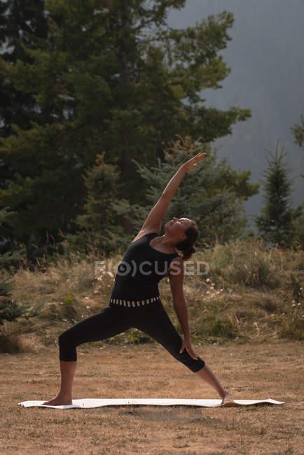 Fit Woman Durchführung Dehnübung auf offenen Boden an einem sonnigen Tag — Stockfoto