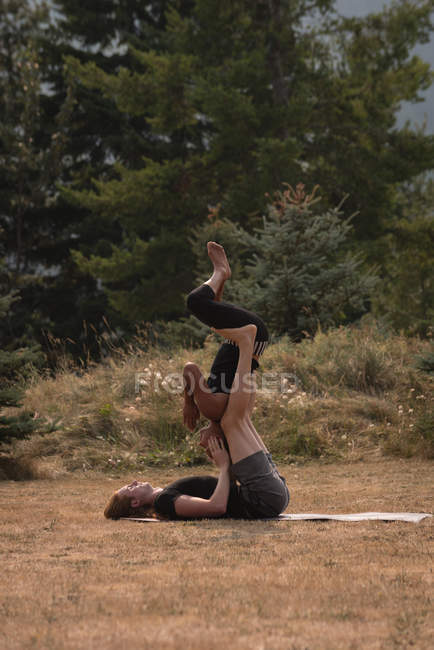 Sporty women practicing acro yoga on an open ground on a sunny day — Stock Photo