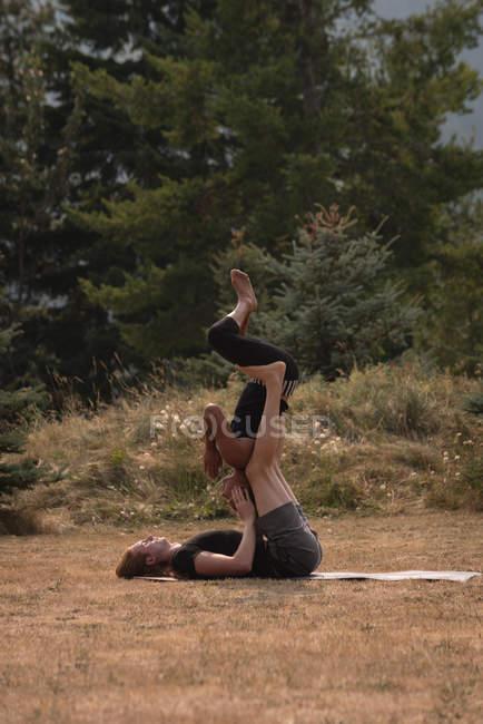 Спортивные женщины, практикующие акройогу на открытой местности в солнечный день — стоковое фото