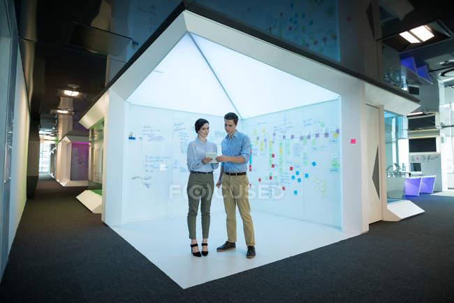 Dirigenti uomini e donne che utilizzano tablet digitali in uffici futuristici — Foto stock