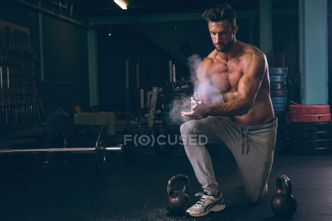 Muscular man rubbing powder in hands in fitness studio — Stock Photo