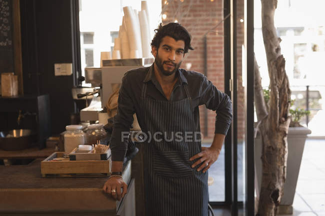 Smiling waiter standing at counter in coffee shop — Stock Photo