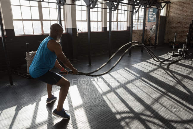 Determined senior man doing cross fit rope training in fitness studio. — Stock Photo