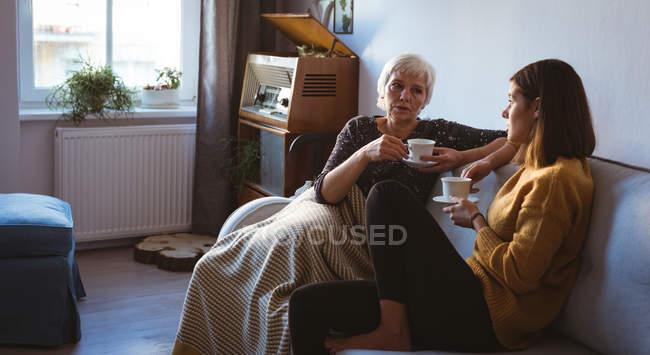 Молодая женщина расслабляющий на диване с чашкой кофе в дневное время — стоковое фото