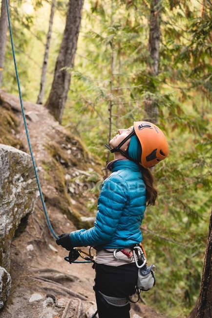 Vista lateral da caminhante feminina se preparando para subir a montanha rochosa — Fotografia de Stock