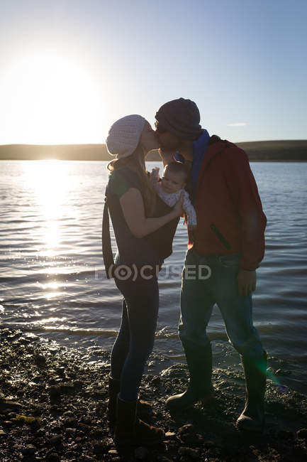 Parents kissing while holding baby near river at sunset. — Stock Photo
