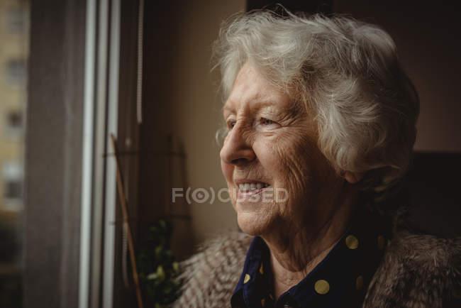 Крупный план улыбающейся пожилой женщины, смотрящей в окно — стоковое фото