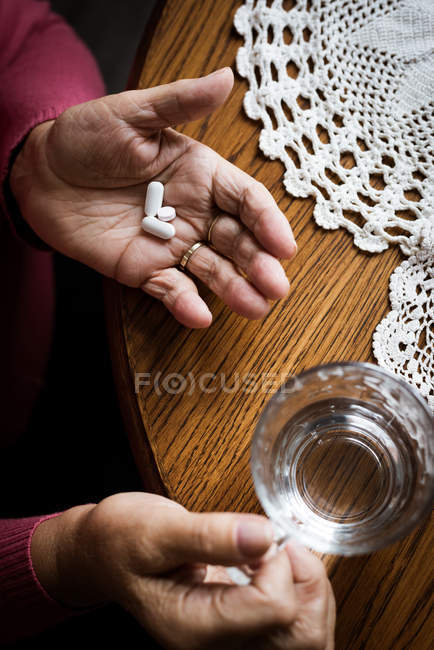 Vista de ángulo alto de las manos de la mujer mayor que toma medicamentos - foto de stock