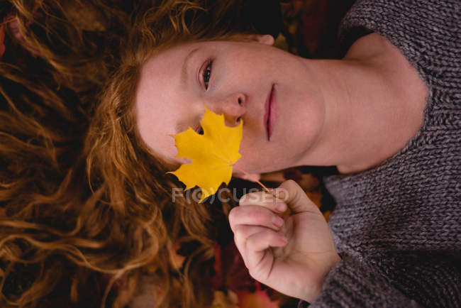 Beautiful woman lying down and holding a maple leaf — Stock Photo