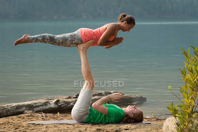 Sporty couple practicing acro yoga near the sea coast on a sunny day — Stock Photo
