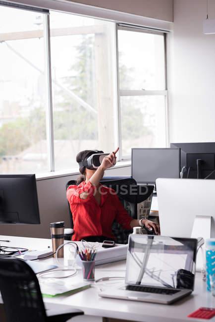 Жіночий офіс виконавчий відчувають віртуальної реальності гарнітуру на столі в офісі творчої — стокове фото