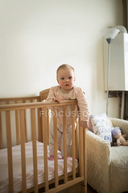 Baby girl standing in crib at home — Stock Photo