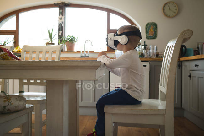 Male child experiencing virtual reality headset in kitchen at home — Stock Photo