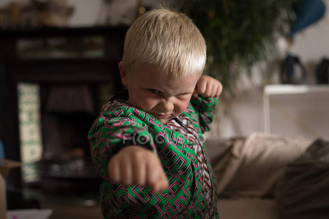 Preschooler boy performing martial arts in living room at home. — Stock Photo