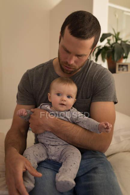 Père tenant bébé garçon assis sur le canapé à la maison . — Photo de stock
