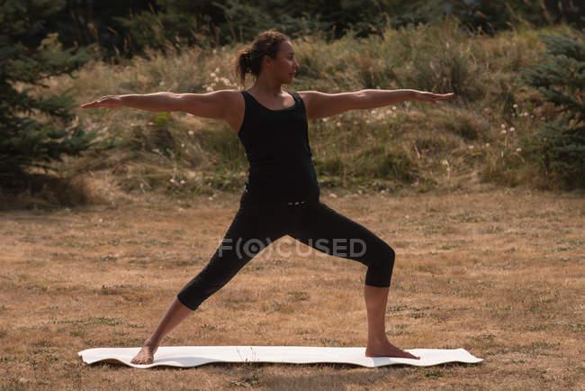 Femme fit exécuter l'exercice d'étirement sur un terrain découvert sur une journée ensoleillée — Photo de stock