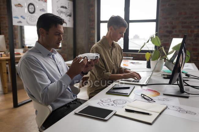 Projetistas automotivos, trabalhando na mesa no escritório — Fotografia de Stock