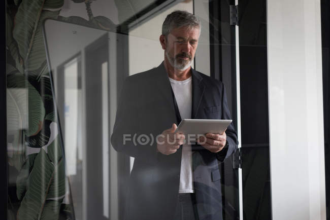 Attentive businessman using digital tablet at creative office — Stock Photo