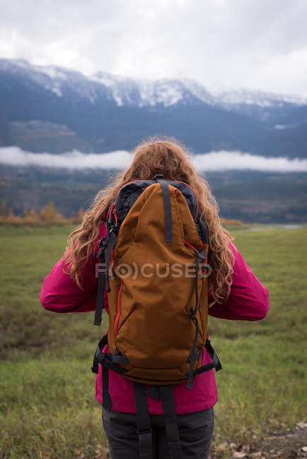 Rear view of Woman with backpack looking at snow-capped mountains — Stock Photo