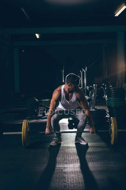 Мускулистый мужчина тренируется с штангой в фитнес-студии — стоковое фото