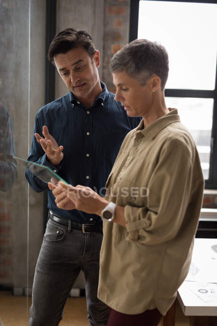 Business colleagues discussing over glass digital tablet in office. — Stock Photo