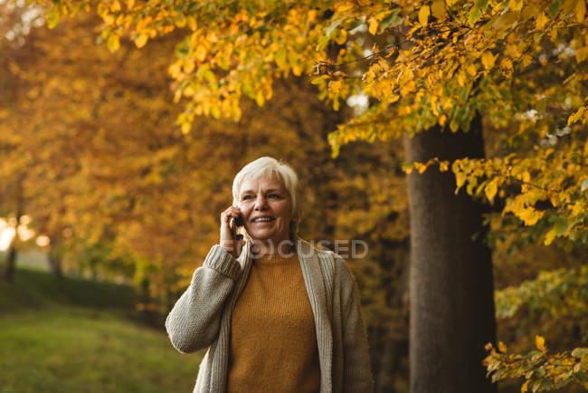Sorridente donna anziana che prende il telefono nel parco durante l'alba — Foto stock