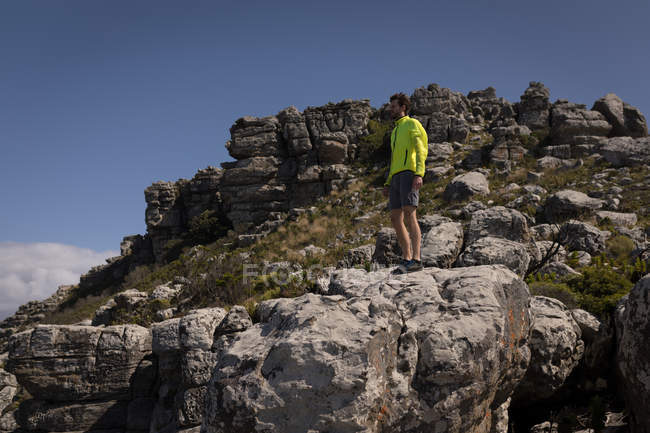 Hiker standing on cliff on a sunny day — Stock Photo