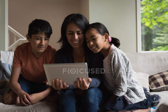 Mother and kids having video call on laptop in living room at home — Stock Photo