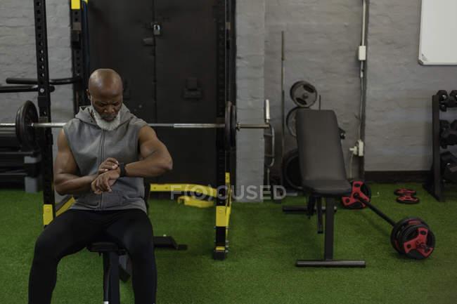 Concentré de senior homme contrôle smartwatch dans la salle de fitness. — Photo de stock