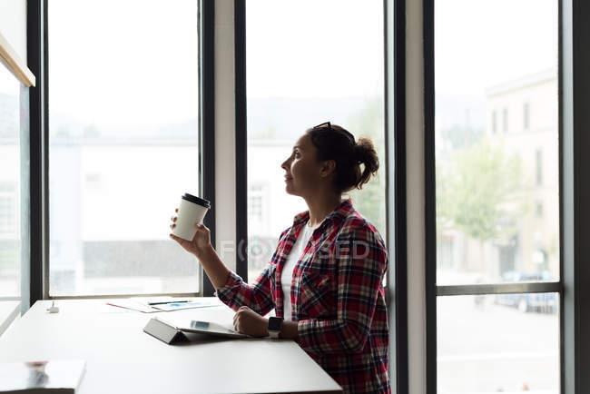 Продуманий жіночий виконавчий з чашкою кави в офісі — стокове фото