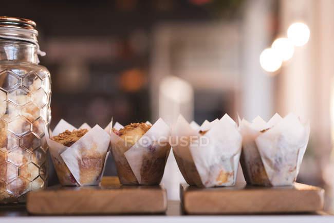 Vista do close-up de muffins na placa de madeira no café — Fotografia de Stock