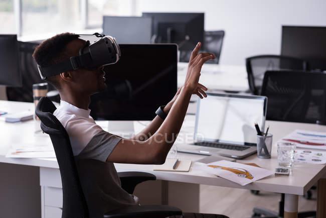 Cadre de bureau utilisant casque de réalité virtuelle sur son bureau dans le bureau — Photo de stock