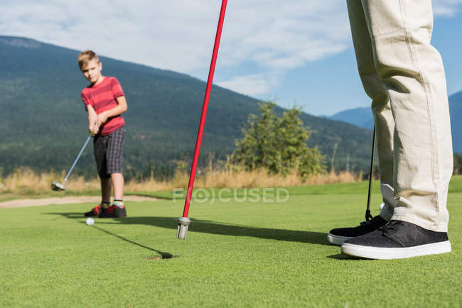 Vater hilft seinem Sohn beim Golfspielen auf dem Platz — Stockfoto