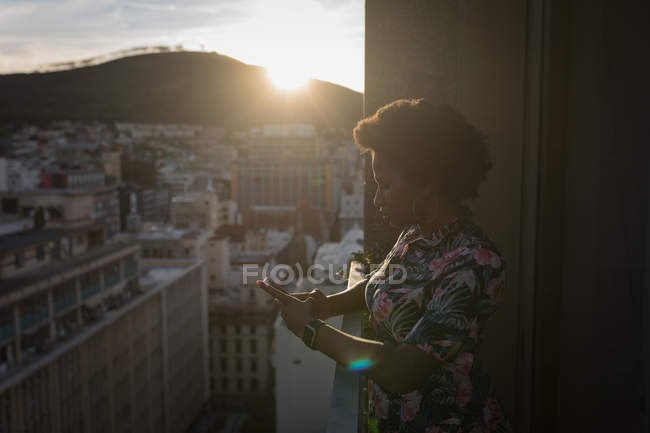 Woman using mobile phone in balcony at sunset. — Stock Photo