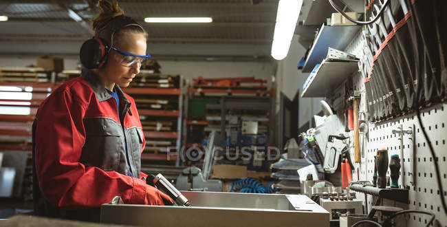Female worker repairing a machine with tool in factory — Stock Photo