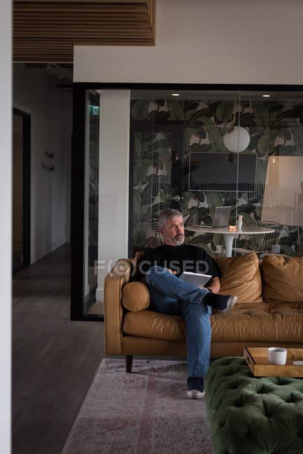 Nachdenklicher Geschäftsmann mit digitalem Tablet auf Sofa im Kreativbüro — Stockfoto
