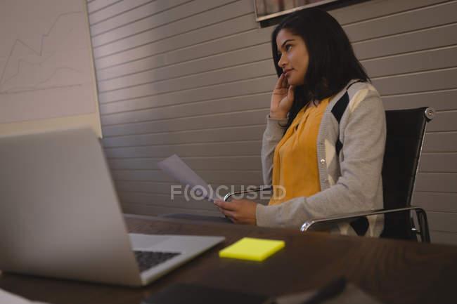 Mujer de negocios hablando por teléfono en la sala de conferencias en la oficina. - foto de stock