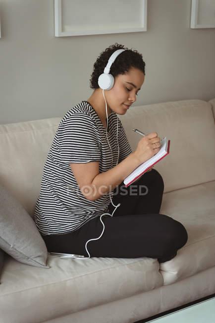 Frau hört Musik, während sie zu Hause in Notizbuch schreibt — Stockfoto