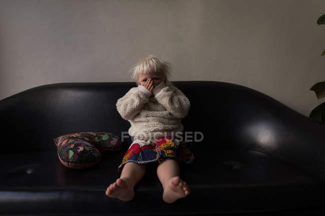 Jeune fille couvrant le visage avec les mains dans le salon à la maison . — Photo de stock