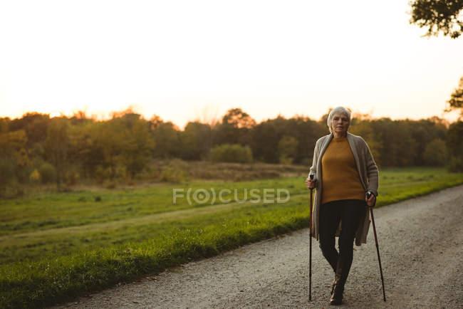 Femme âgée marchant sur une route poussiéreuse avec des bâtons de marche au moment de l'aube — Photo de stock