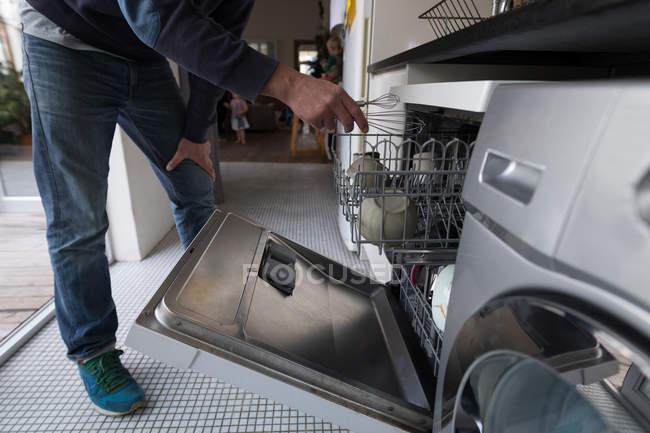 Homme mettant moustaches à l'intérieur chariot lave-vaisselle dans la cuisine à la maison . — Photo de stock