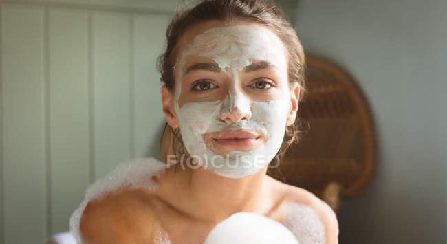 Frau mit Gesichtsmaske badet im heimischen Badezimmer. — Stockfoto