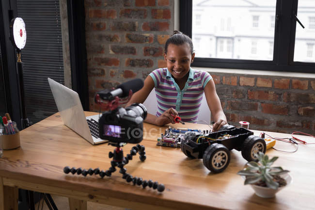 Pre-adolescent blogger girl soldering circuit board of electric toy car in office. — Stock Photo
