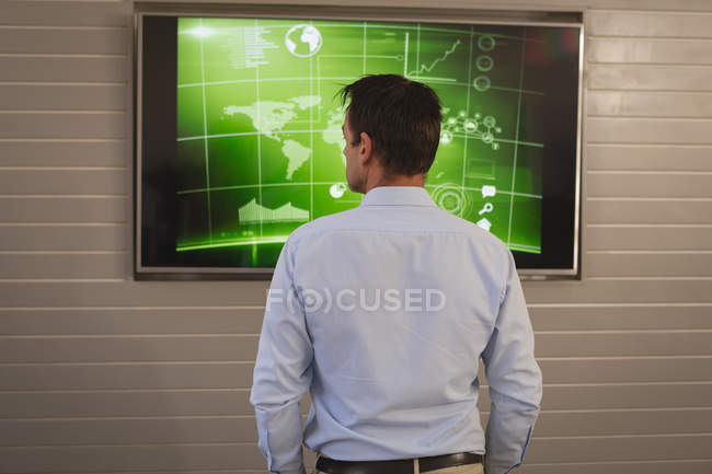Rear view of businessman looking at screen with graph analyzing at office. — Stock Photo