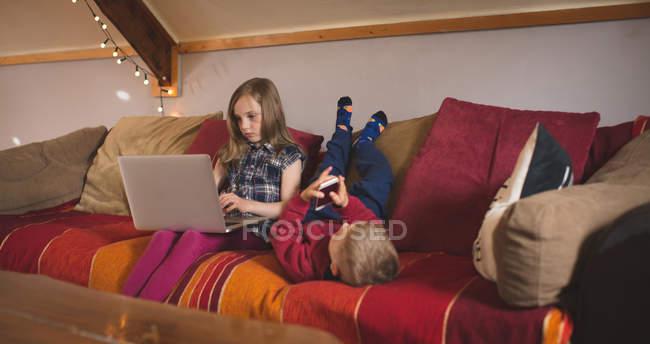 Sorellina utilizzando dispositivi multimediali sul divano di casa — Foto stock