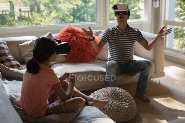 Father and daughter using virtual reality headset in living room at home — Stock Photo